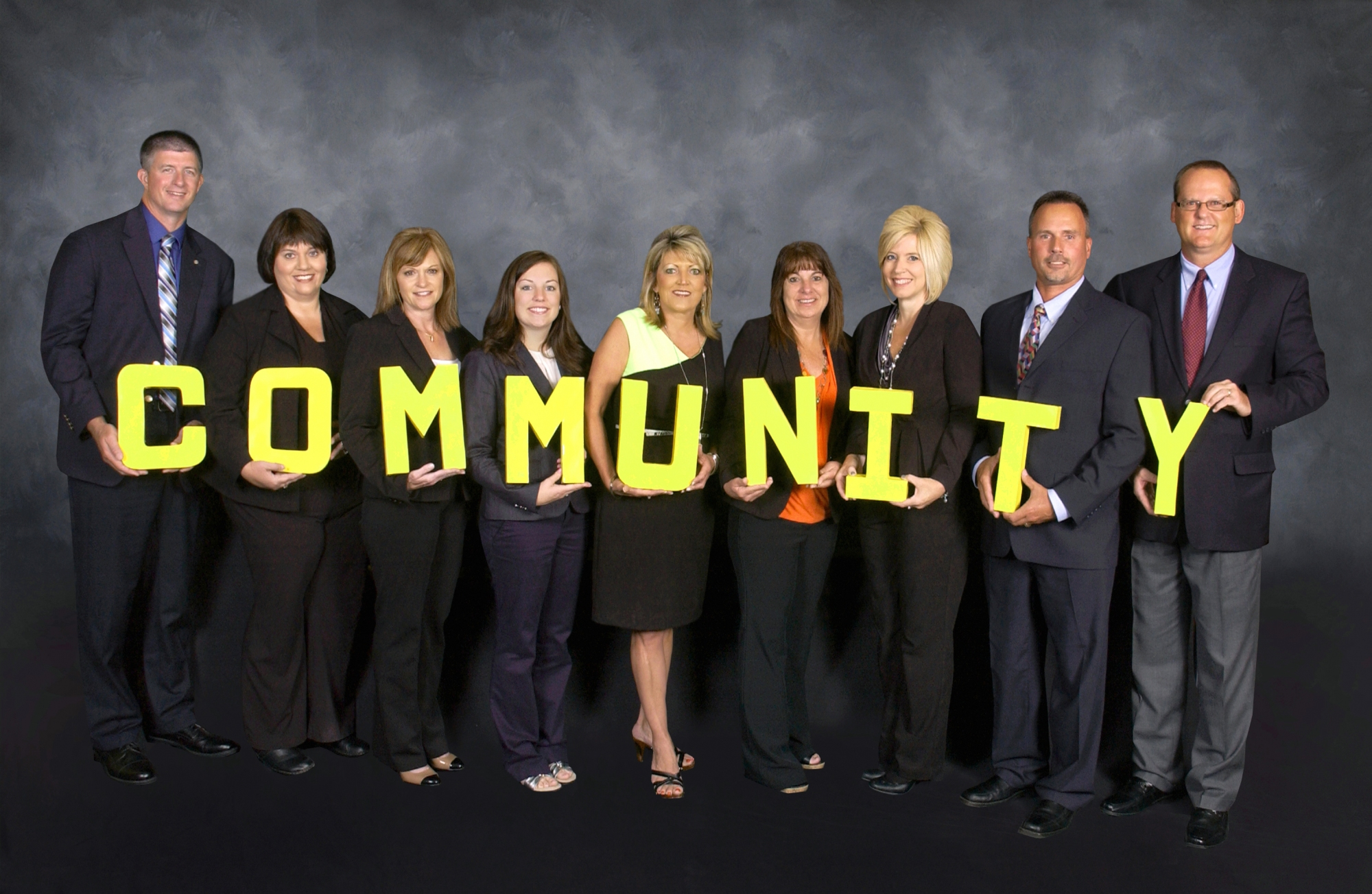 "Group of people holding the letters to spell ""community"""