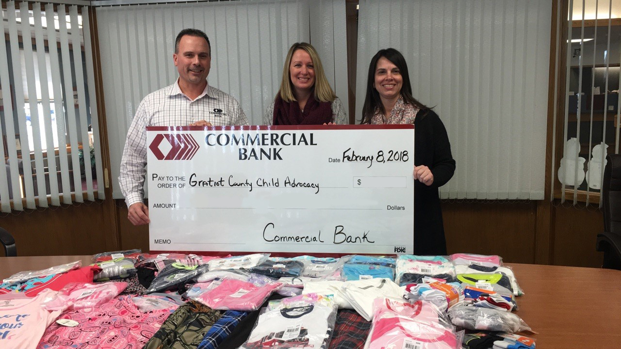 Employees holding a large check from Commercial Bank for Gratiot County Child Advocacy