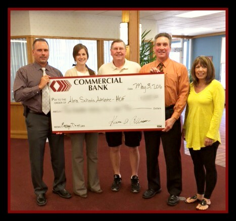 Employees holding a check from Commercial Bank to Alma Schools Hall of Fame Scholarship Fund