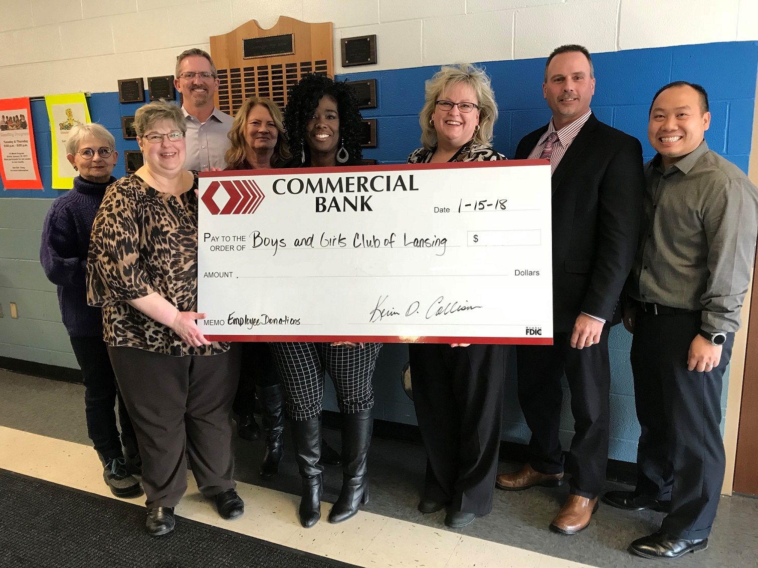 Employees holding a check from Commercial Bank to Boys and Girls Club of Lansing, Michigan.