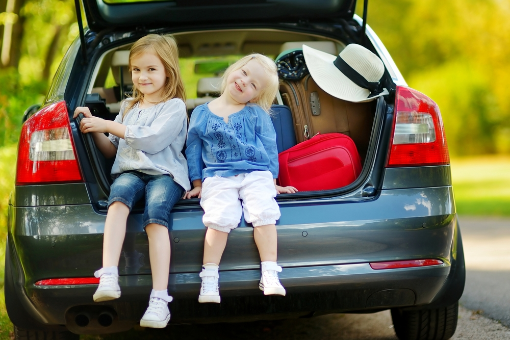 Two young girls smiling, sitting on back of car with the hatch up