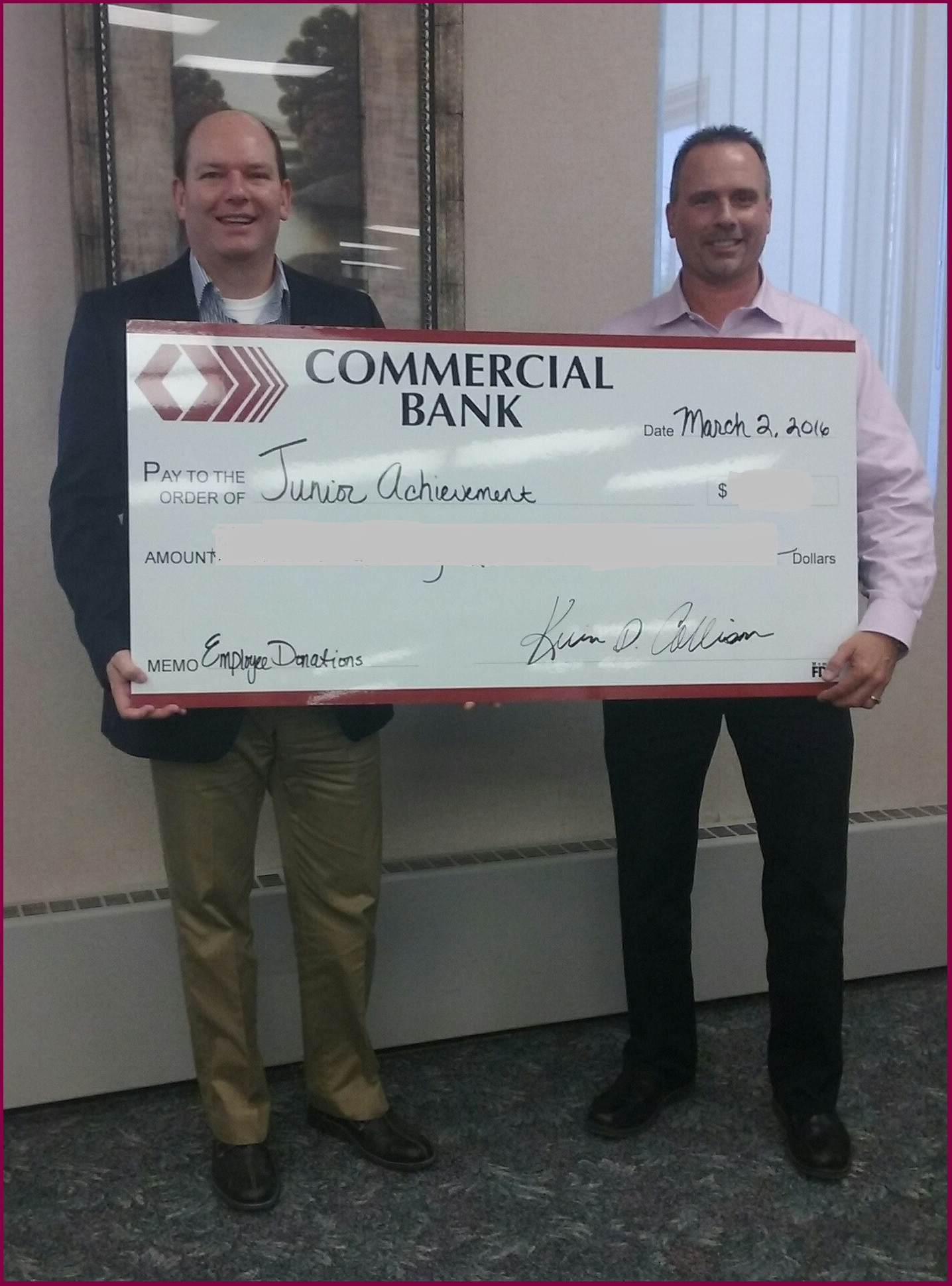 Employees holding a check from Commercial Bank to the Junior Achievement of Central Michigan
