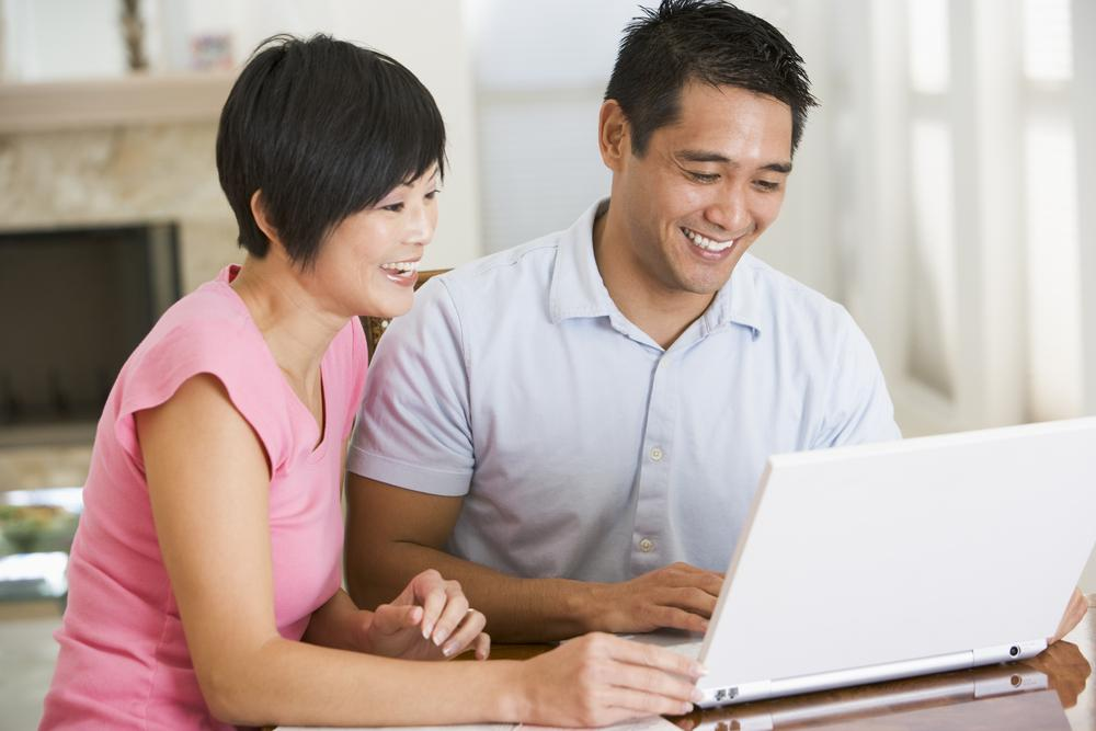 Couple looking at laptop doing online banking