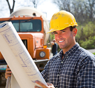 Worker holding blueprints with cement truck in background