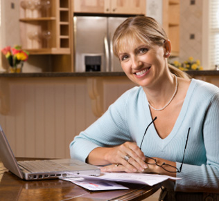 Woman sitting with laptop and mail at kitchen table